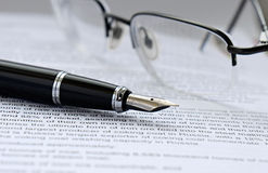 Pen and glasses. On the paper with text Stock Photo