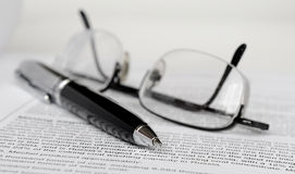 Pen and glasses. On paper Royalty Free Stock Image