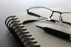 Pen and glasses. On the notebook Stock Images