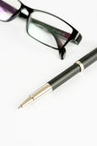 Pen and glasses, on a background Stock Photography