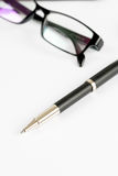Pen and glasses, on a background Royalty Free Stock Images