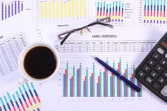 Pen, glasses, calculator and cup of coffee on financial graph, business concept Stock Images