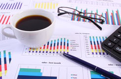 Pen, glasses, calculator and cup of coffee on financial graph, business concept Stock Photo