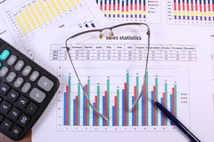 Pen, glasses and calculator on financial graph, business concept Royalty Free Stock Images