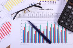 Pen, glasses and calculator on financial graph, business concept Stock Images