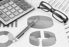 Pen, glasses and calculator on paper table Royalty Free Stock Images