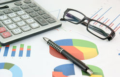 Pen, glasses and calculator on paper table with di Stock Images
