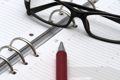 Pen and glasses on calendar event Royalty Free Stock Images