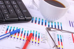 Pen, glasses, computer keyboard and cup of coffee on financial graph, business concept Royalty Free Stock Photography