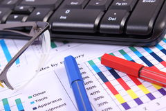 Pen, glasses and computer keyboard on financial graph, business concept Royalty Free Stock Images
