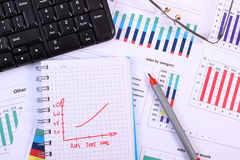 Pen, glasses and computer keyboard on financial graph, business concept Stock Images