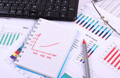 Pen, glasses and computer keyboard on financial graph, business concept Royalty Free Stock Image