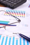 Pen, glasses and computer keyboard on financial graph, business concept Stock Photos