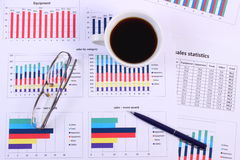 Pen, glasses, and cup of coffee on financial graph, business concept Royalty Free Stock Photo