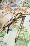 Pen and glasses with euro banknotes. Royalty Free Stock Photo