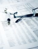 Pen and glasses on financial chart Stock Image