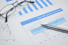 Pen and glasses on financial chart and graph, accounting backgro Royalty Free Stock Photos