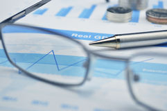 Pen and glasses on financial chart and graph Royalty Free Stock Photo