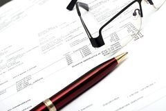 Pen and glasses on financial report Royalty Free Stock Image