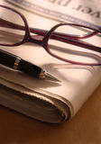 Pen and Glasses on Newspaper stock photos