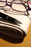 Pen and Glasses on Newspaper Stock Images