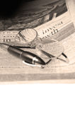 Pen and glasses and newspaper. Pen and glassesand newspaper over white glass table Royalty Free Stock Photo