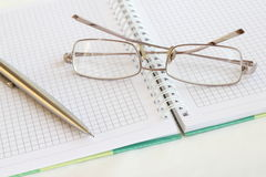 Pen and glasses on a notepad Stock Photos