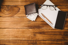 Pen and glasses on notepad next to wallet and smartphone Royalty Free Stock Photo
