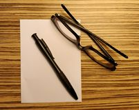 Pen and glasses spectacle. On white paper with wood texture Royalty Free Stock Photos