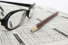 Pen and glasses on a sudoku game Royalty Free Stock Photo
