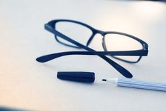 Pen and glasses on white paper in blue tone royalty free stock images