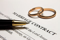 Pen and gold rings on the contract Stock Photography