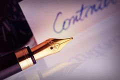Pen with golden nib. With contract document in the background Stock Photo