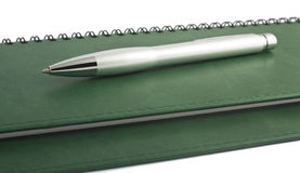 Pen on green spiral notepad. Silver pen on green spiral notepad on white Stock Photo