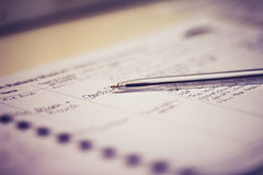 Pen and guestbook with handwriting. Selective focus on pen and guestbook with handwriting royalty free stock image