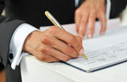 Pen in hand of man writing on the notebook Royalty Free Stock Photos