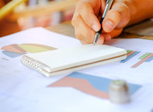 Pen in hand on notebooks with coins placed on Stock Photography