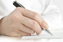 Pen in hand writing on the page Royalty Free Stock Photography
