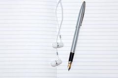 Pen and headphones Royalty Free Stock Photo