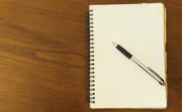 Pen hierboven gezet op notitieboekje blanco pagina op houten lijstachtergronden stock foto's