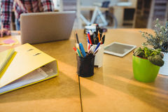 Pen holder with pens and file on table Royalty Free Stock Image