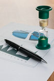 Pen and hourglass on the table Stock Images