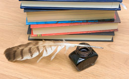 Pen, ink and books on a wooden board Royalty Free Stock Photo