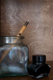 Pen and ink. Pen, glass and ink on wooden background Royalty Free Stock Image