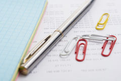 The pen and a jotter on the backing with numbers Royalty Free Stock Photography