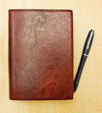 Pen and journal. Black pen and red leather journal on desk Stock Photo