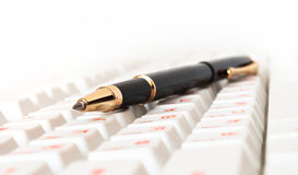 Pen on an  keyboard Stock Photos