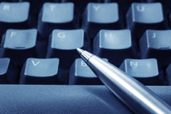 Pen on Keyboard. Ballpoint pen resting on computer keyboard.  Blue tone, focus on pen tip Stock Image