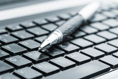 Pen on the keyboard Stock Image