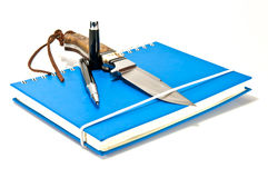 Pen and knife on notebook Stock Image